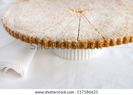 Traditional homemade Scottish shortbread. Fresh baked shortbread circle, cut into petticoat tails (triangular shapes) and sprinkled with fine sugar. Sweet teatime dessert for Christmas or Easter. - stock photo