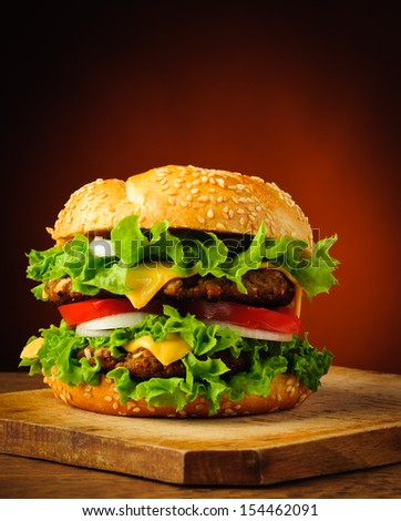 traditional homemade tasty hamburger or cheeseburger on a wooden plate - stock photo