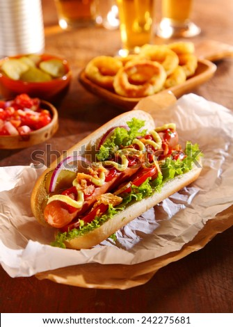 Traditional hot dog with a smoked frankfurter on a fresh roll garnished with mustard and ketchup and served with lettuce, tomato and onion - stock photo