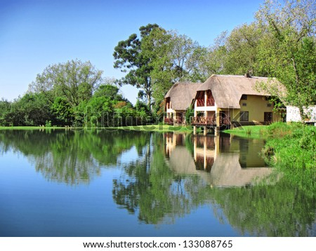 Traditional house next to lake. Shot in Monks Cowl area, Drakensberg Mountains, South Africa. - stock photo