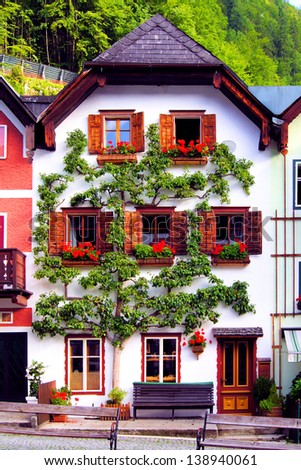 Traditional house with flowers in Hallstatt village, Austria - stock photo