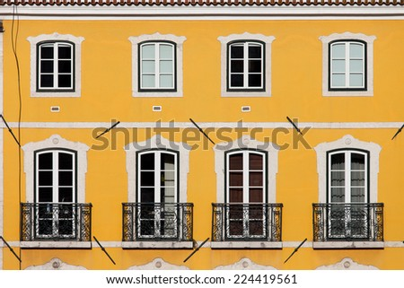 Traditional house with yellow facade and tall windows with balconets in Lisbon, Portugal.
