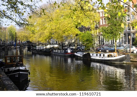 Traditional Houses and house boat along canal in Amsterdam, Holland - stock photo