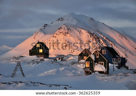 Traditional houses in the Kulusuk village in sunset light, winter, Greenland - stock photo