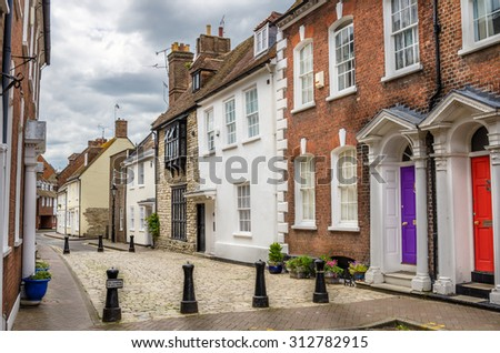 Traditional Houses on a Cobbled Pedestrian Street in England and Cloudy Sky - stock photo