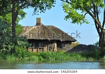 Traditional houses with thatched roof in the Danube delta - stock photo