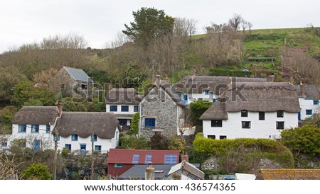 Traditional housing with whitewashed walls and thatched roofs in an ancient fishing community in Cornwall UK