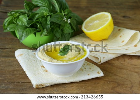 traditional hummus dip of chickpea with pita bread on a wooden table - stock photo