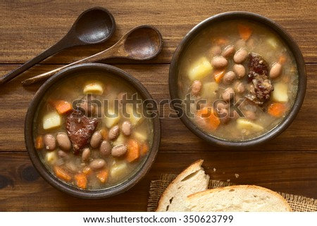 Traditional Hungarian Babgulyas (bean goulash) soup made of pinto beans, smoked meat, potato, carrot, csipetke (homemade soup pasta), garlic, onion, photographed overhead with natural light - stock photo