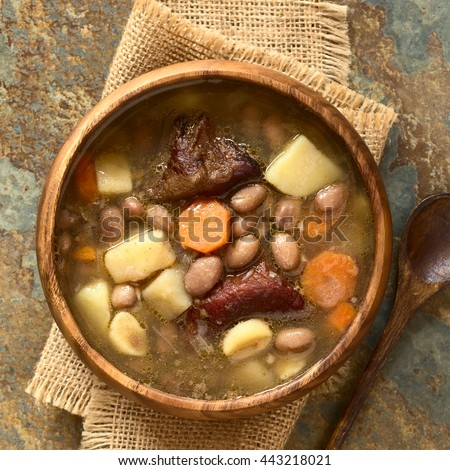 Traditional Hungarian Babgulyas bean goulash soup made of pinto beans, smoked meat, potato, carrot, csipetke (homemade soup pasta), garlic, onion, photographed overhead on slate with natural light