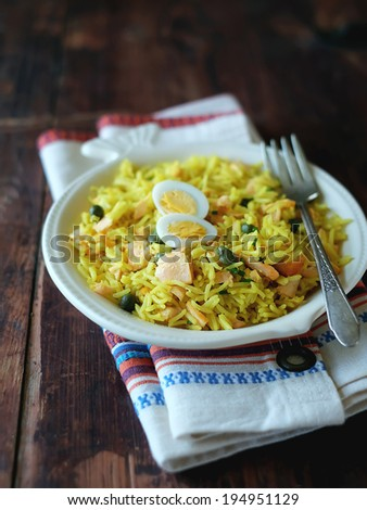 Traditional indian dish Kedgeree with cooked basmati rice, smoked salmon or trout fish, onion, garlic, milk, curry powder and served with hard-boiled eggs in a plate for lunch or dinner - stock photo