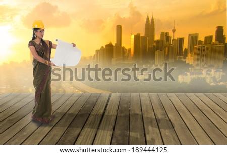 traditional indian female engineer with kuala lumpur city background - stock photo