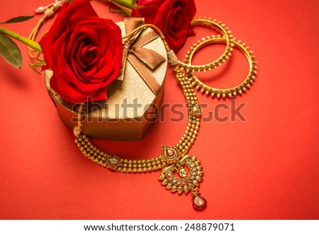 Traditional indian gold necklace and bangles set arranged with heart-shaped gift box and red rose flowers. - stock photo