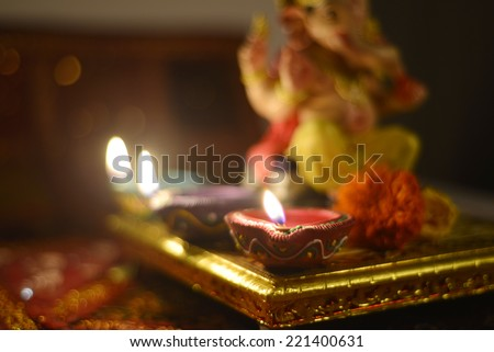 Traditional indian lamps burning in front of a Ganesha idol - an out of focus treatment - stock photo