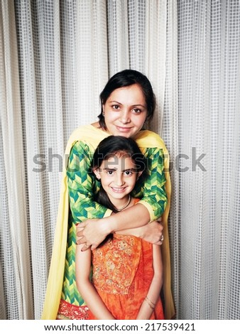 Traditional Indian mother hugging her daughter. - stock photo