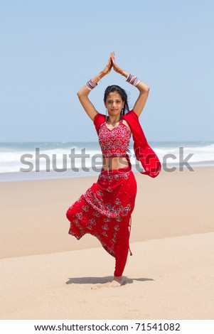 traditional Indian woman doing yoga on beach - stock photo