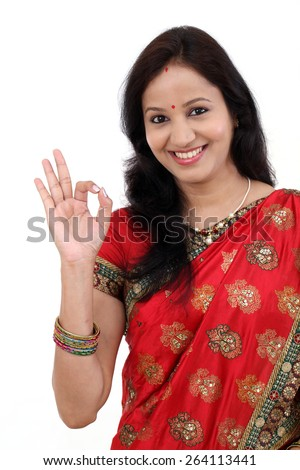 Traditional Indian Young woman making OK sign against white background - stock photo