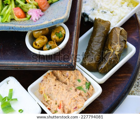 Traditional Israeli breakfast (fresh vegetable salad, green olives, tuna salad, labneh yogurt, cottage cheese, stuffed grape leaves, etc) at seaside cafe in Tel Aviv (Israel). - stock photo