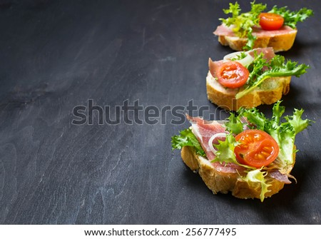 Traditional Italian antipasti crostini with ham, salad and tomato. Selective focus. Space for text - stock photo