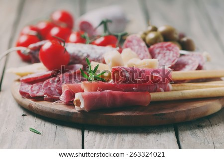Traditional italian antipasto with prosciutto, cheese, olive and sausage, selective focus and toned image - stock photo