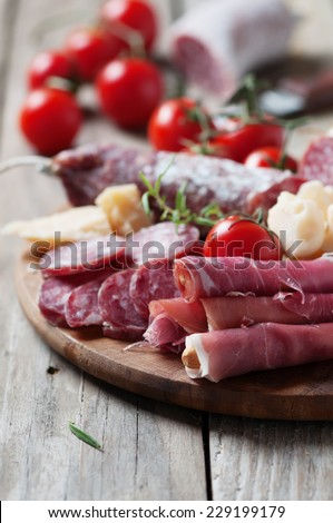 Traditional italian antipasto witn sausage, cheese, prosciutto and olive, selective focus - stock photo