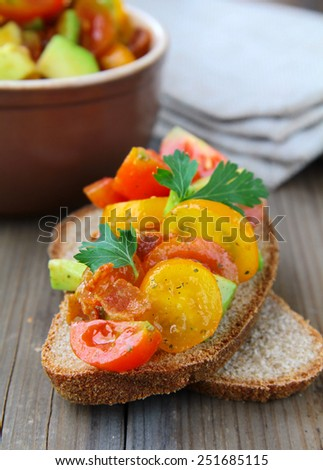 traditional Italian appetizer of bruschetta with tomato and avocado - stock photo