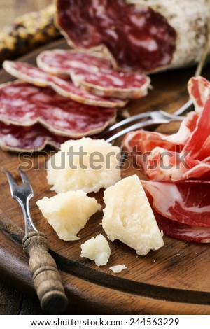 Traditional Italian appetizer - parmesan cheese, cold cut prosciutto ham and cured salami on a rustic wooden cutting board - stock photo