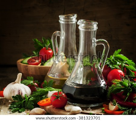 Traditional Italian balsamic vinegar in a glass carafe, still life with fresh vegetables on a dark background, selective focus - stock photo