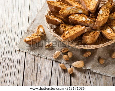 Traditional Italian biscotti Almond Cantuccini in a basket decorated with nuts on wooden table