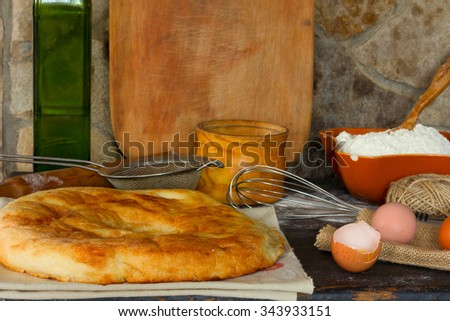 Traditional Italian bread, focaccia, broken egg with the yolk, whole eggs on the background of a stone wall with utensils. Rustic style. Side view close-up. Selective focus. - stock photo