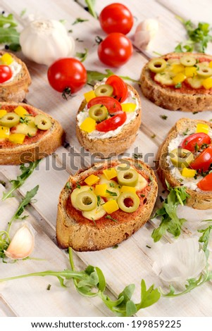 Traditional Italian bruschettas on the wooden board from above.Selective focus on the front bruschetta - stock photo