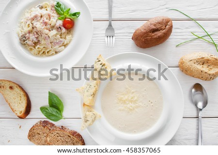 Traditional italian dinner in restaurant, flat lay. Cheese cream-soup and spaghetti carbonara served with bread on white wooden background. European cuisine concept - stock photo