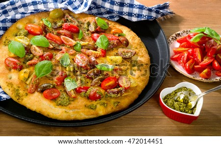 Traditional Italian focaccia with tomatoes, basil and pesto. View from above