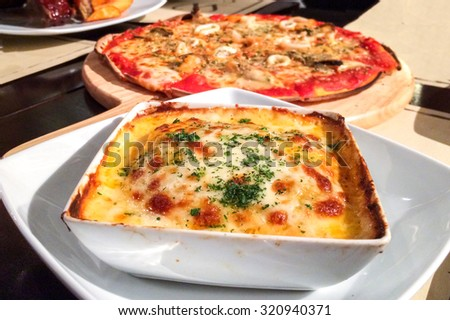 Traditional Italian Lasagna made with Minced Beef Bolognese Sauce topped with Basil Leaves served on a White Plate with Blur Pizza in Background