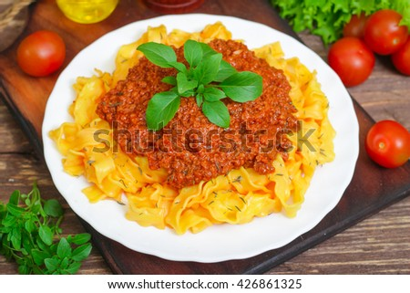 Traditional Italian pasta Bolognese or Bolognese with cooked pasta noodles topped with a spicy tomato based meat sauce garnished with fresh basil on a wooden background - stock photo