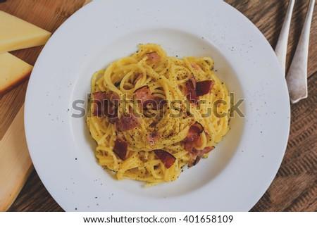 Traditional italian pasta spaghetti alla carbonara with bacon, cheese and egg yolk on white plate - stock photo
