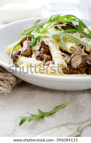 Traditional italian pasta with mushrooms and arugula in white bowl