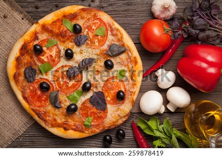 Traditional italian pizza margherita with tomatoes, pepper, olives and basil on vintage rustic background