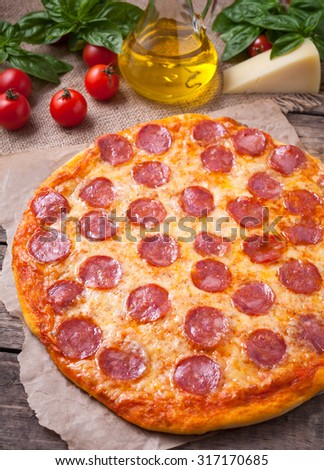 Traditional Italian pizza pepperoni with delicious crust on vintage wooden table background. Rustic style and natural light. - stock photo
