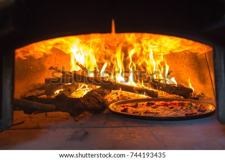 traditional Italian pizza wood oven with raw pizza and large fire in the background