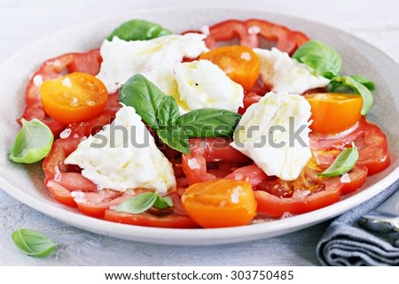 Traditional Italian salad with tomatoes,mozzarella and basil. Selective focus - stock photo