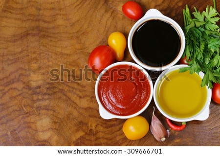 traditional Italian sauces - balsamic vinegar, tomato sauce and olive oil - stock photo