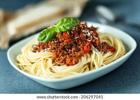 Traditional Italian spahgetti Bolognaise or Bolognese with cooked pasta noodles topped with a spicy tomato based meat sauce garnished with fresh basil - stock photo