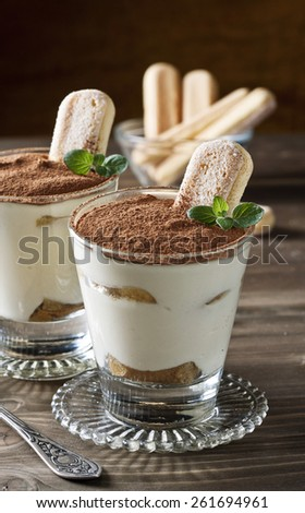 Traditional Italian Tiramisu dessert in glass on a wooden table - stock photo