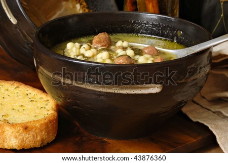 Traditional Italian wedding soup in rustic stoneware bowl with toasted garlic bread.  Close-up with shallow dof. - stock photo