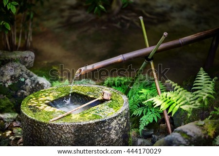 Traditional japanese bamboo fountain Ryoan-ji tsukubai at Ryoan-ji temple in Kyoto, Japan. The basin provided for ritual washing of the hands and mouth.