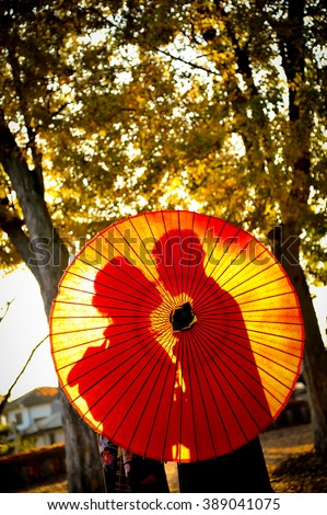 Traditional Japanese ceremony wedding lovely day, silhouettes of married couple holding red paper umbrella in hands, kissing under golden sunset in shrine temple garden, colorful maple ginko leaves - stock photo