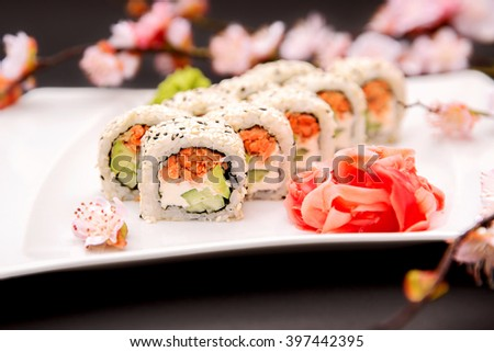 Traditional Japanese food - sushi rolls with grilled salmon,  avocado, cucumber, cream cheese and sakura on a dark background - stock photo