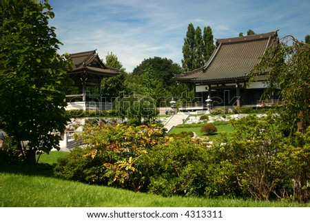 traditional japanese garden with buddhist temple and bell tower - stock photo