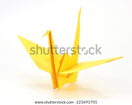 Traditional Japanese origami crane made of yellow paper over white background - stock photo